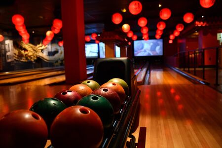 Bowling lane and balls in the row in bowling center.