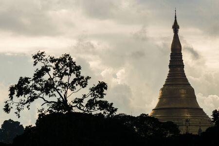 Blick auf die Silouhette-Spitze der Shwedagon-Pagode in Myanmar mit Wolken und Baum