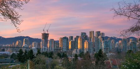 sun going down over skyline Vancouver downtown with the mountains of north Vancouver in the background
