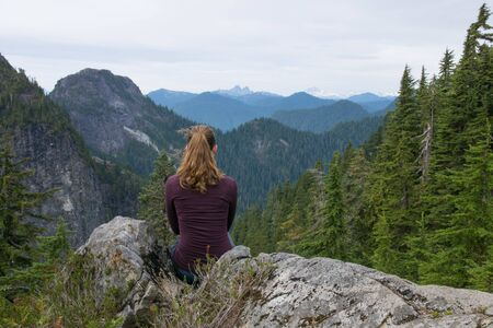 female hiker enjoying mountain view from top of the mountain in late summer around North Vancouver