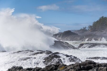 big wave crashing at the rocks and cliff of the coast on sunny Vancouver island