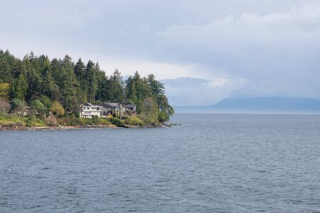 houses at cliff , rainy and foggy mountain and forest view over coast and bay near Vancouver island at Nanaimo, Canada 写真素材