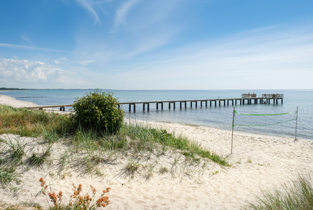 voyage: Idyllic beach with long pier at bright and warm summer day in southern Sweden.