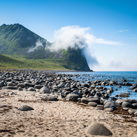 Scenic view from the beach with mountains against the blue sky in the Lofoten, Norway