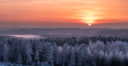 Winter landscape with frosty trees and beautiful sunset at evening time in Finland Archivio Fotografico