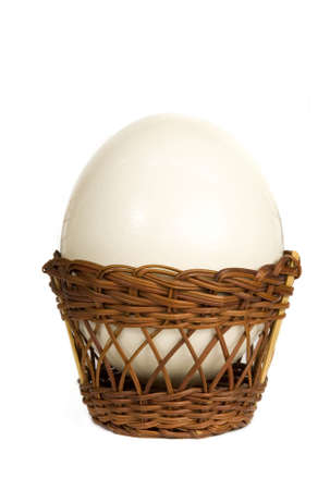 gigantic: Ostrich egg in a wicker basket on white background