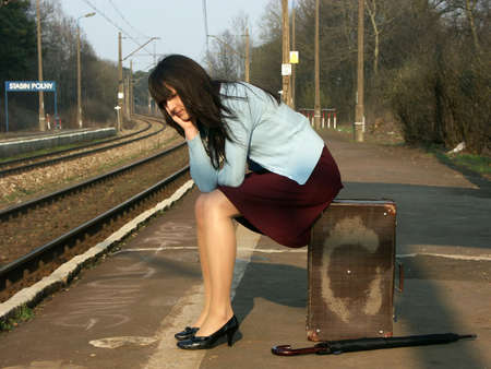 depart: Young girl waiting for the train on the empty railway platform with an old suitcase