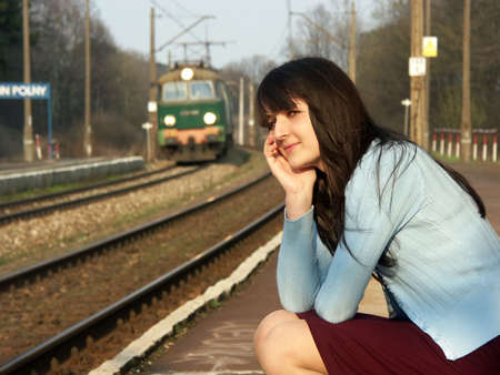 Young girl waiting for the train on the empty railway platform with an old suitcase