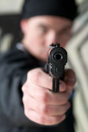 straight man: Young man pointing a gun straight at the camera. Focus is on the gun.