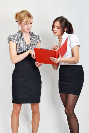 Two cute female students reading the document Stock Photo - 13169911