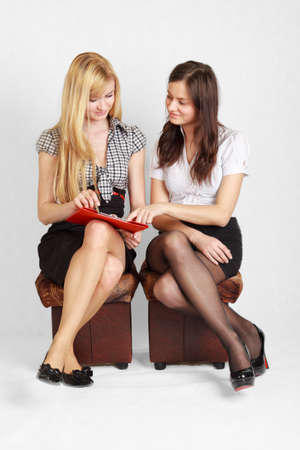 secretary skirt: Two cute female students reading the document and smiling