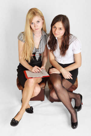 Two cute female students reading the document and smiling photo