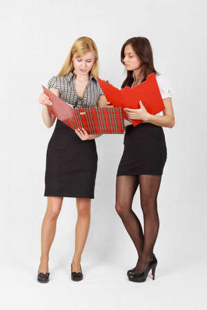 Two cute female students reading the documents photo