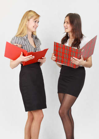secretary skirt: Two cute female students reading the documents and smiling Stock Photo