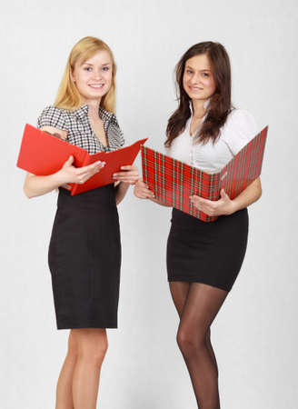 Two cute female students reading the documents and smiling Stock Photo