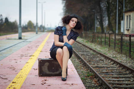 Girl waiting for train on empty railroad platform photo