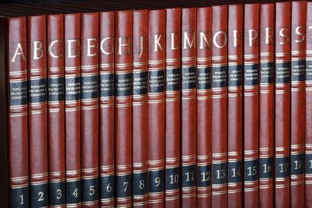 Row of encyclopedia books. Focus on volume \