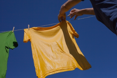 Hands putting shirts on clothesline to dry Stock Photo - 15043323