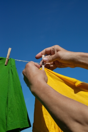 Hands putting shirts on clothesline to dry  Stock Photo - 15043311