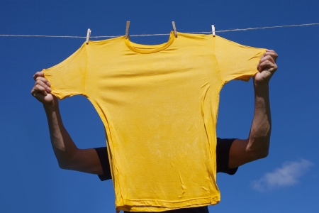 Hands putting shirts on clothesline to dry Stock Photo - 15043321