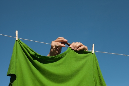 Hands putting green t- shirts on clothesline to dry  photo