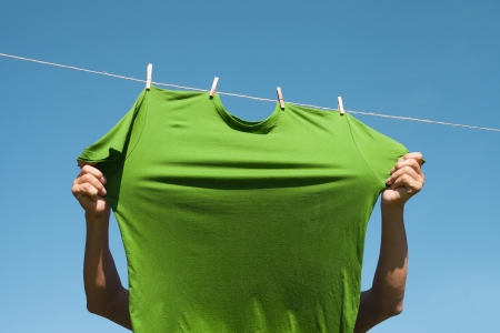 Hands putting green t- shirts on clothesline to dry  Stock Photo - 15043318