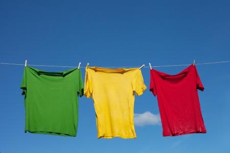 T-shirts on clothesline against blue sky  Archivio Fotografico