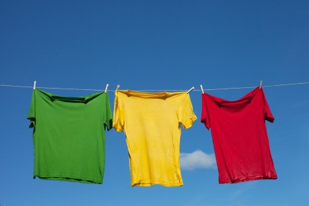 T-shirts on clothesline against blue sky  版權商用圖片