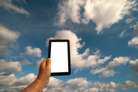 Computer in hand against cloudy sky Stock Photo - 15043328