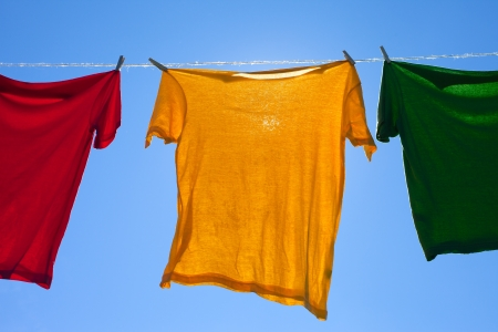 clothes line: Shirts on clothesline against blue sky  Stock Photo