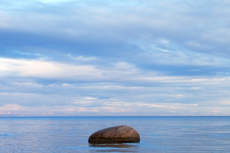 Lonely stone in blue Baltic sea  photo