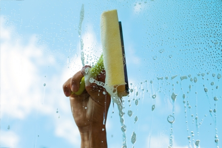 Human hand washing window in nice summer day  photo