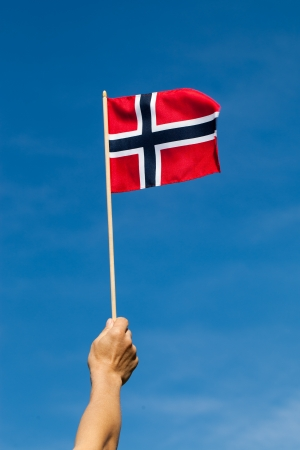 Norway flag in hand against blue sky  photo