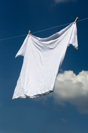 White shirt on clothesline against blue sky.