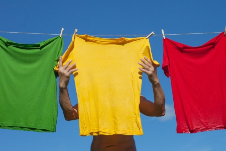 Multicolor shirts on clothesline in sunny day. photo