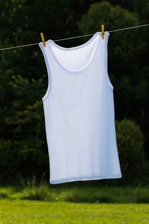 White shirt hang on clothesline against green. photo
