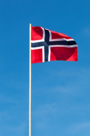 norwegian flag: Norwegian flag against blue sky.