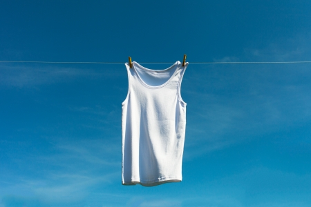 White shirt drying against blue sky. Stock Photo