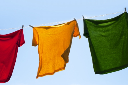 Wet shirts on clothesline against sunlight. photo