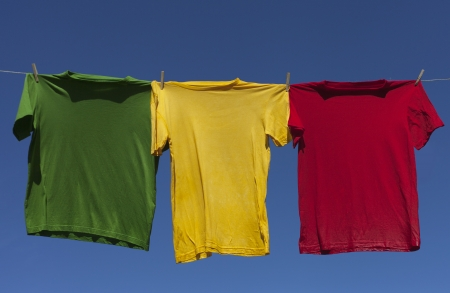 Wet shirts on clothesline against blue sky. photo