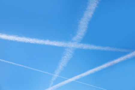 Plane trails in blue sky. photo