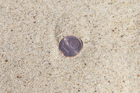 Euro coin in dry sand.