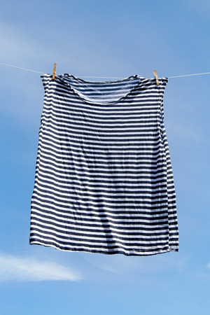 Wet striped shirt on clothesline against blue sky. photo