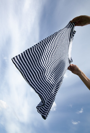 Wet striped shirt in hands against blue sky. photo