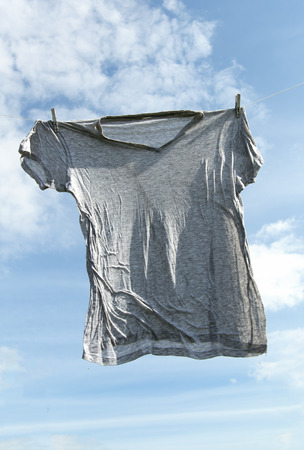 Wet  shirt on clothesline against cloudy sky. photo