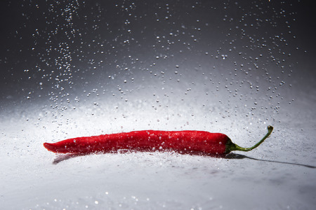 Flying water drops and red pepper. Stock Photo