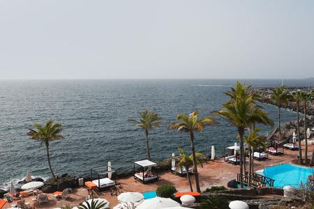 adeje: Pool and palms at Atlantic ocean in Costa Adeje, Tenerife, Canary islands, Spain.
