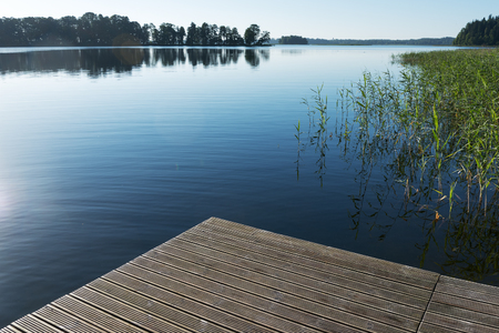 calm water: Empty pier at calm water. Stock Photo