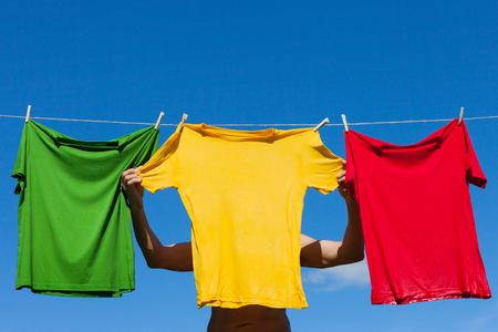 Hanging of wet shirts on clothesline. Stock Photo
