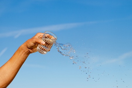 Glass of pouring water against blue sky. Stock Photo